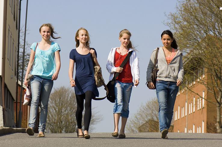Fyra barn som går i bredd på en väg