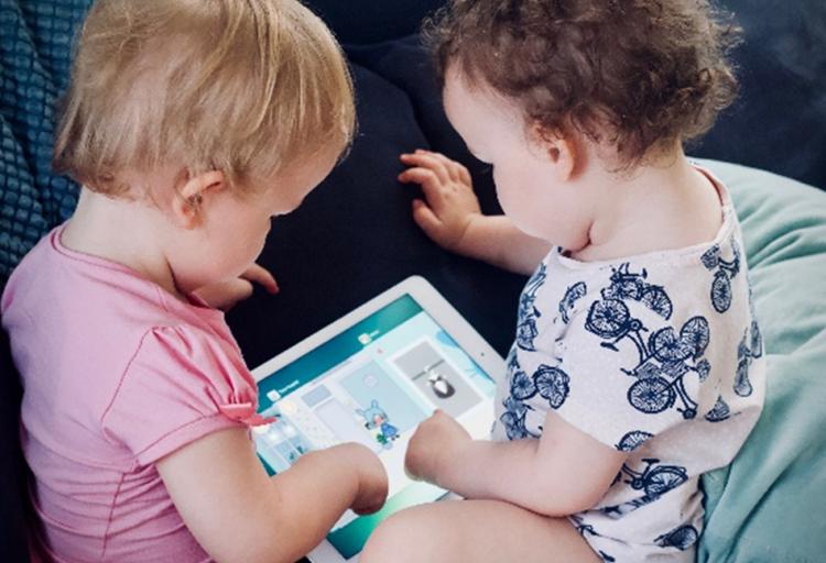 Två små barn tittar tillsammans på en läsplatta