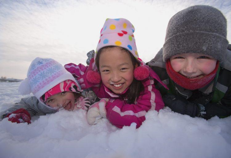 Tre barn som leker i snön