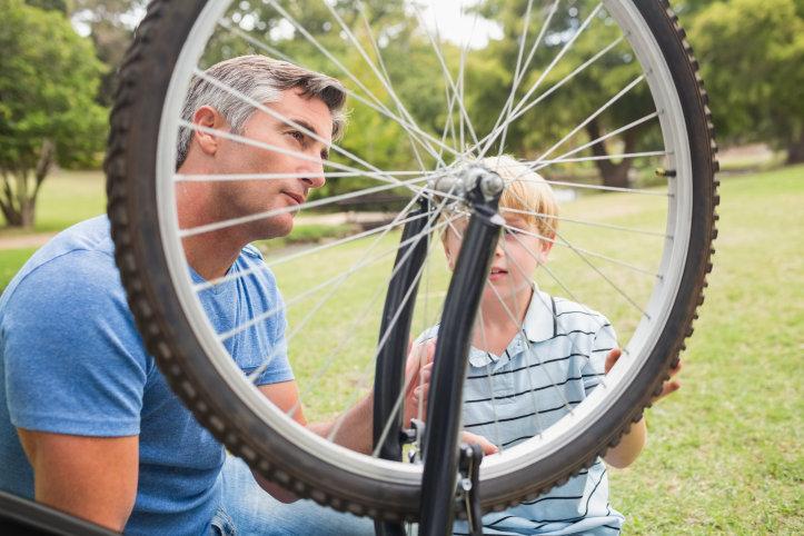 En pappa och son reparerar en cykel