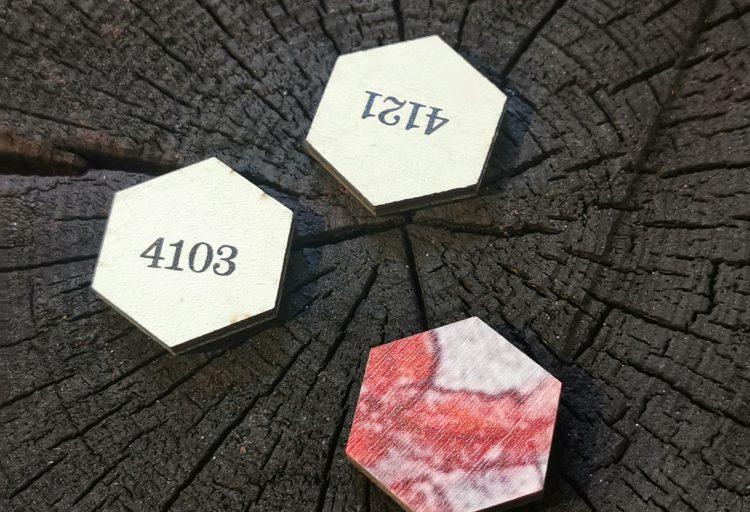 Tre brickor på en stubbe. Två av brickorna har var sitt nummer på sig, den tredje en del av en bild, som en pusselbit.