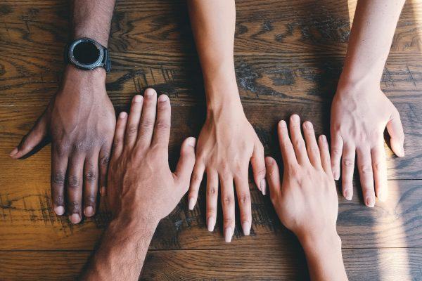 fem händer som möts på ett bord