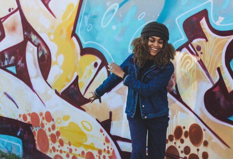 En ung kvinna framför en vägg med graffitti.