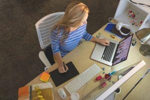 Bild på en kvinna som sitter och jobbar vid dator.