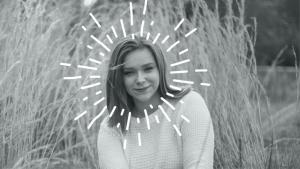 Bilden föreställer en ung kvinna utomhus, i bakgrunden vajande säd, runt hennes huvud en målad aura av strålar