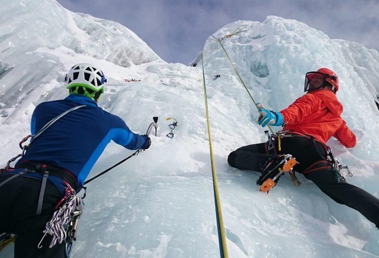 Två personer som ägnar sig åt bergsklättring vintertid
