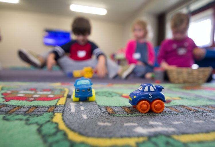 Tre barn och några leksaker på en förskola