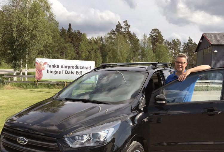 """Martin Carling vid en biogasbil framför en skylt med texten """"Tanka närproducerad biogas i Dals-Ed""""."""